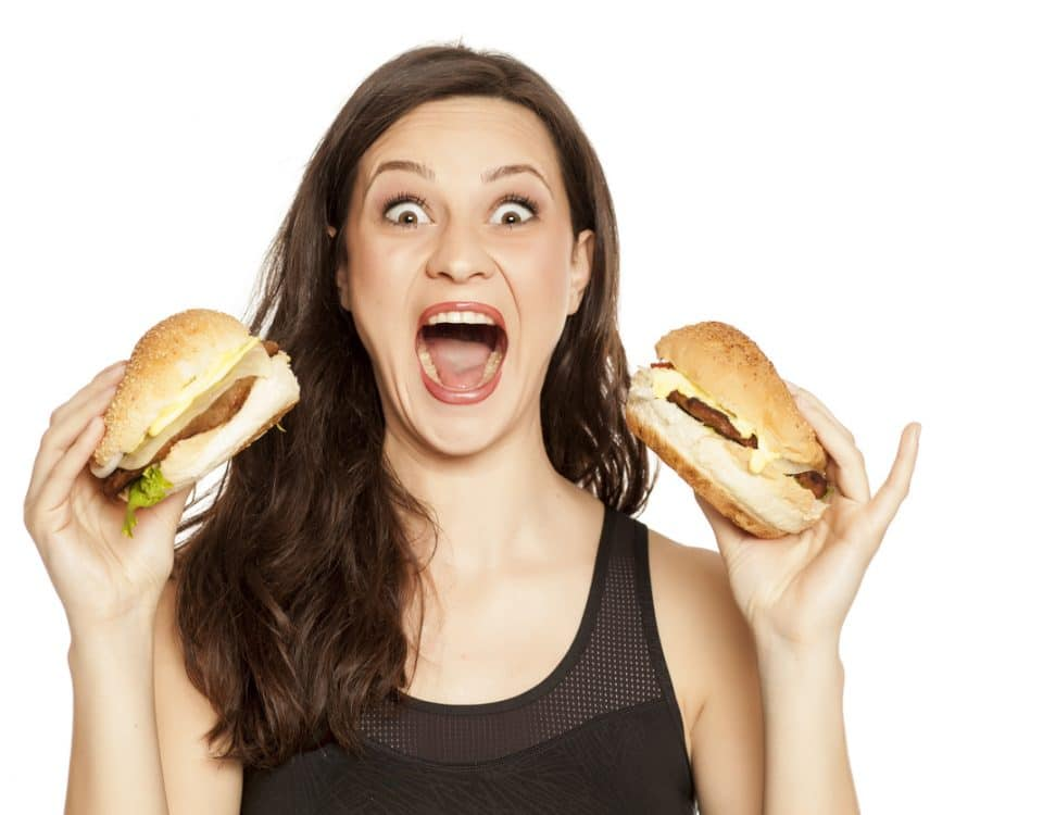 young beautiful greedy woman holding two burgers on white background